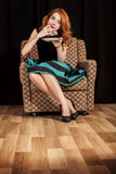 Redhead girl secretly eating cake. Stock Images