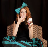 Redhead girl secretly eating cake. Royalty Free Stock Photography