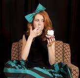 Redhead girl secretly eating cake. Royalty Free Stock Photography