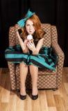 Redhead girl secretly eating cake. Royalty Free Stock Photos