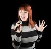 Redhead girl singing karaoke. Happy beautiful redhead girl singing on a microphone, karaoke Stock Images
