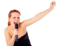 Redhead girl sings into a microphone Royalty Free Stock Image