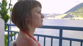 Redhead girl sitting the balcony of hotel and looking to lagoon sea stock footage