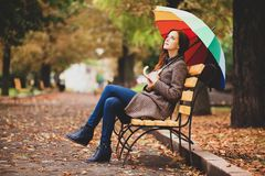 Redhead girl sitting at bench in autumn park. royalty free stock images