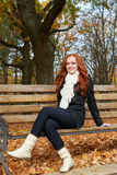 Redhead girl sitting on a bench in city park, autumn season Stock Images