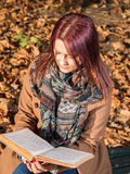 Redhead girl sitting on bench in park Royalty Free Stock Image