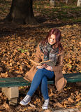 Redhead girl sitting on bench in park. Happy redhead girl sitting,smiling and reading a book on bench in park Royalty Free Stock Images