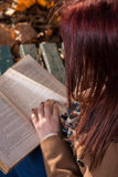 Redhead girl sitting on bench in park and reading book Stock Photo
