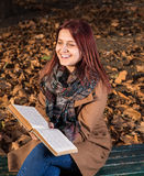 Redhead girl sitting on bench in park and reading book. Happy redhead girl sitting,smiling and reading a book on bench in park Stock Image