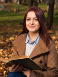 Redhead girl sitting on bench in park and reading book Stock Photos