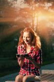 Redhead girl sitting in city park and having fun communicate via tablet PC Stock Photo
