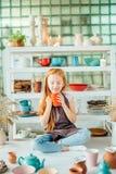 Redhead girl sitting at clay workshop studio with many cup. Little redhead girl sitting at clay workshop studio with many cup Stock Photos