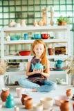 Redhead girl sitting at clay workshop studio with many cup. Little redhead girl sitting at clay workshop studio with many cup Royalty Free Stock Photo