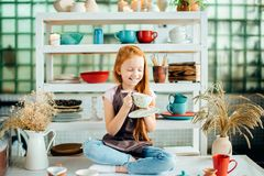 Redhead girl sitting at clay workshop studio with many cup. Little redhead girl sitting at clay workshop studio with many cup Royalty Free Stock Photography