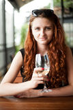 Redhead girl sitting with a glass of dry white wine in a cafe Stock Photography