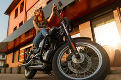 Redhead girl sitting on a motorcycle Stock Photo
