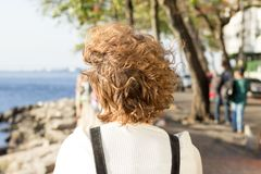 Redhead girl sitting on Mureta da Urca, Rio de Janeiro, Brazil, contemplating the sea. stock image