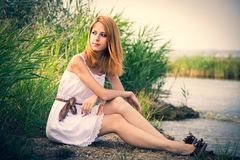 Redhead girl sitting near river. In white dress royalty free stock photography