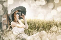 Redhead girl sitting near tree with vintage camera. Stock Photography