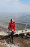 The redhead girl sitting on the old tree at the sea Stock Image
