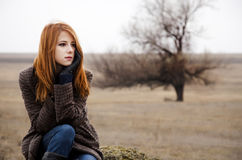 Redhead girl sitting at outdoor in autumn time. Royalty Free Stock Image