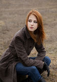 Redhead girl sitting at outdoor in autumn time. royalty free stock photos