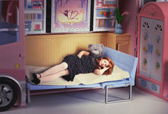 Redhead girl sleeping in a doll bed royalty free stock photo
