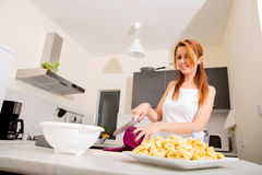 Redhead girl slicing in kitchen Stock Photo