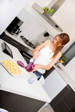 Redhead girl slicing in kitchen. Portrait of a redhead girl slicing in the kitchen Royalty Free Stock Images