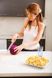 Redhead girl slicing in kitchen Stock Images