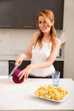 Redhead girl slicing in kitchen Royalty Free Stock Photo