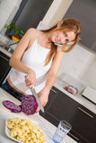 Redhead girl slicing in kitchen telephoning Royalty Free Stock Image