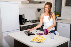 Redhead girl slicing in kitchen touching tablet pc Royalty Free Stock Photo