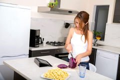 Redhead girl slicing in kitchen watching tablet pc Stock Image