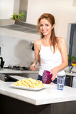 Redhead girl slicing in kitchen watching tablet pc Royalty Free Stock Photography