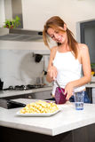 Redhead girl slicing in kitchen watching tablet pc Royalty Free Stock Images