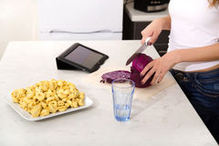 Redhead girl slicing in kitchen watching tablet pc Royalty Free Stock Photos