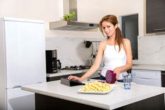 Redhead girl slicing in kitchen watching tablet pc Stock Photo