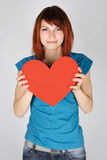 Redhead girl smiling and holding red paper heart Stock Photography