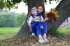 Redhead girl with son Autumn leaves royalty free stock photography