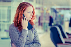 Redhead girl speaking by phone. Royalty Free Stock Image