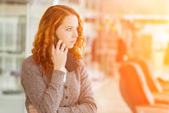 Redhead girl speaking by phone. Stock Photo