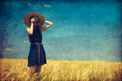 Redhead girl at spring field with retro camera. Stock Images