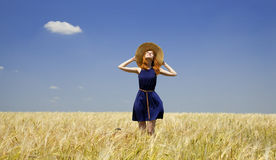 Redhead girl at spring wheat field. Royalty Free Stock Image