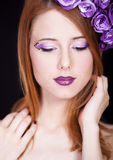 Redhead girl with style make-up and flowers Stock Photography