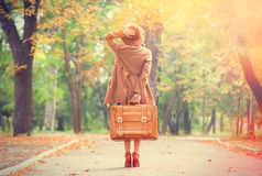 Redhead girl with suitcase. In the autumn park Stock Image