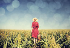 Redhead girl with suitcase at corn field. Stock Photo