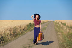 Redhead girl with suitcase at countryside road Stock Photography