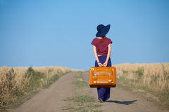 Redhead girl with suitcase at countryside road. Near wheat field Stock Photography