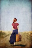 Redhead girl with suitcase at countryside road. Near wheat field. Photo in old color image style stock image